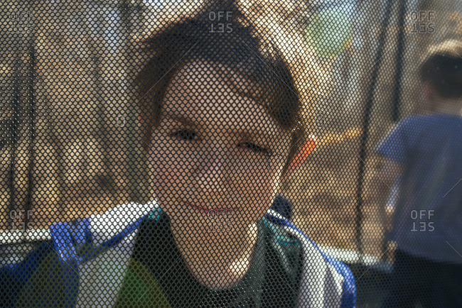 Child looking through the net of an enclosed trampoline