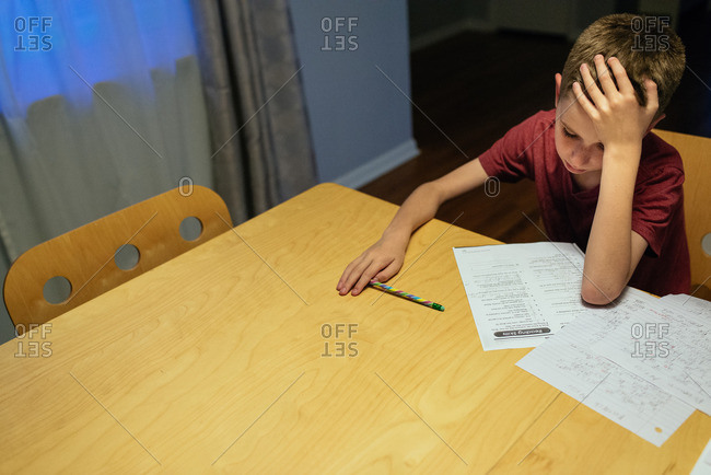 Boy looking at his homework in frustration