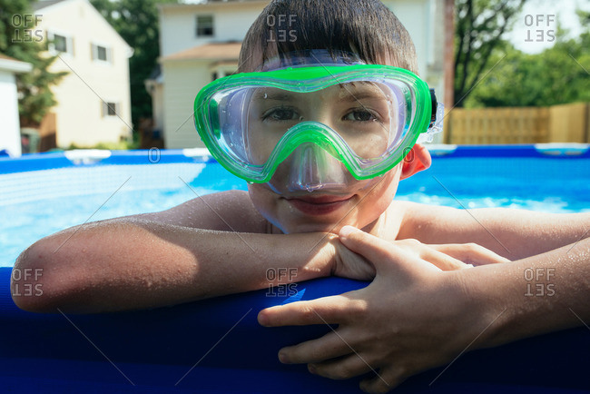 Boy wearing swim goggles looking over the edge of a swimming pool