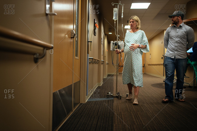 Pregnant woman walking with her husband in a hospital hallway during pre-labor