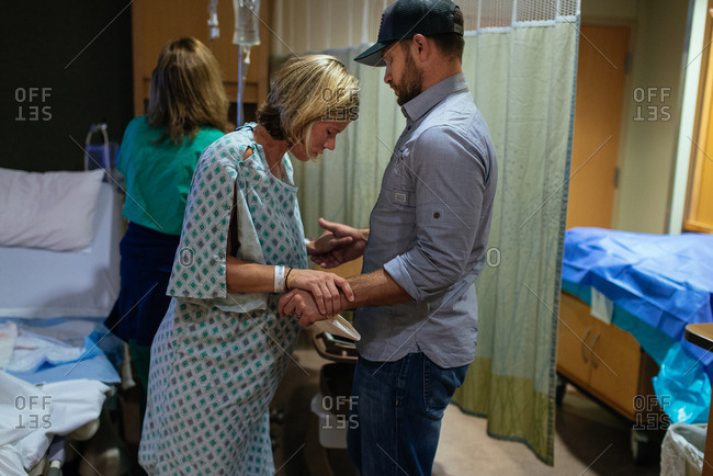 Pregnant woman being supported by her husband in a hospital room during pre-labor