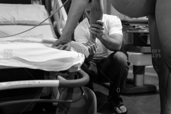 Pregnant woman leaning on a hospital bed and holding her husband during pre-labor