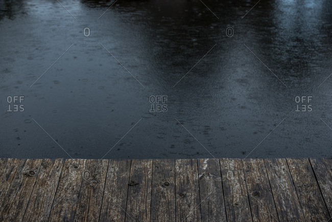 Raindrops on water surface and wooden pier