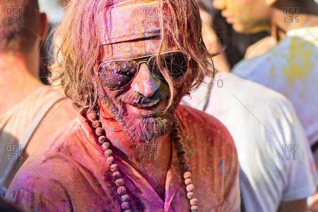 Madrid, Spain - August 13, 2016: Portrait of cheerful bearded man in sunglasses and beads with face in different colors. During Jubilant people celebration, Holi Festival of Monsoon, in the district of Lavapies, Madrid