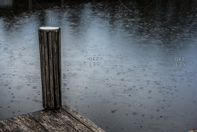 Wooden pier with pole against of water surface covered with raindrops