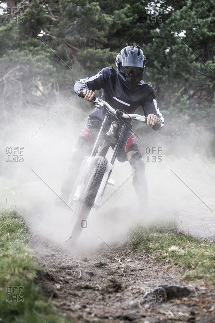 Mountain biker riding downhill with a dust cloud