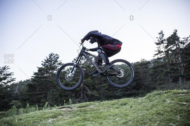 Mountain biker riding downhill jumping midair