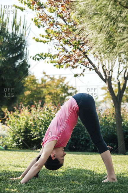 Young woman practicing yoga in the park- downward Facing Dog Position