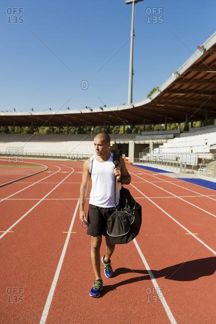 Young sportsman walking on tartan track