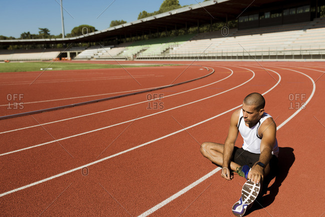 Young sportsman stretching on tartan track