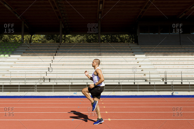 Young sportsman running on tartan track