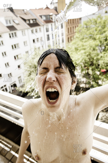 Screaming woman on balcony showering herself with water