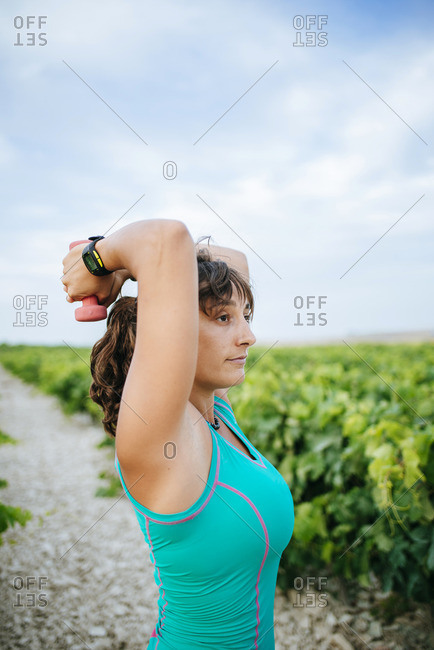 Woman doing sport with weights in a vineyard