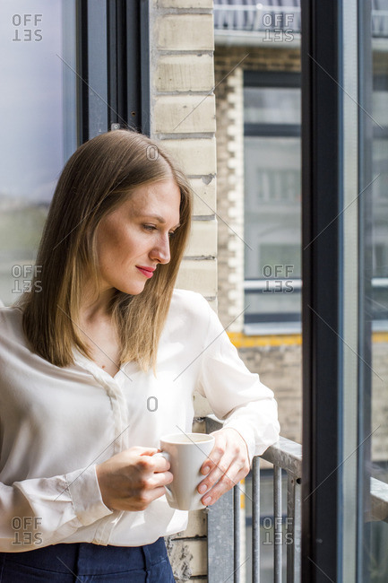 Woman with coffee mug standing at open window looking down