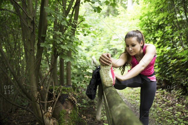 Sportive young woman stretching in forest