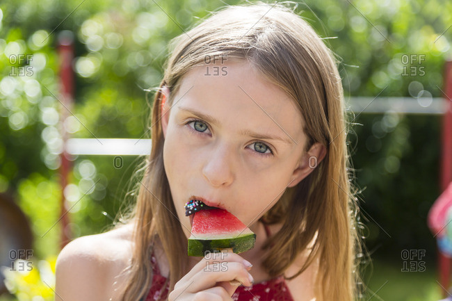 Portrait of girl eating iced watermelon lolly