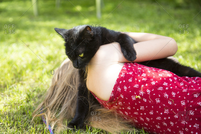 Back view of little girl lying on meadow with black cat