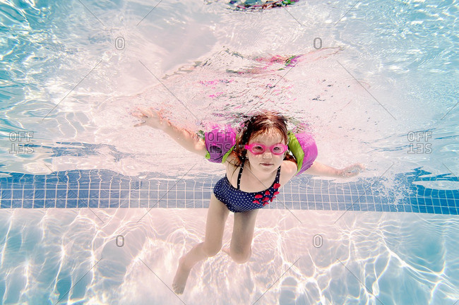 Little girl swimming underwater in a pool