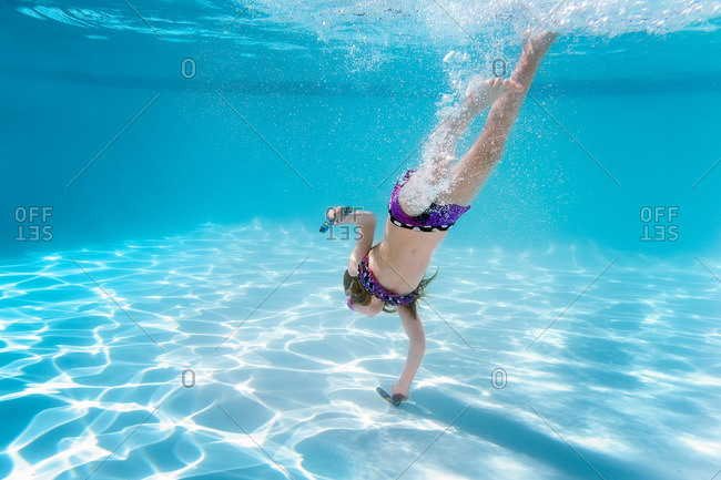 Little girl diving into a swimming pool