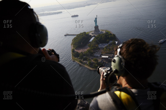July 28, 2015: Photographers taking photos of the Statue of Liberty on Ellis Island from a helicopter