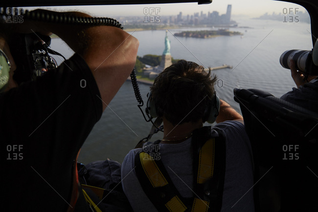 July 28, 2015: Group of photographers taking photos of the Statue of Liberty on Ellis Island from a helicopter