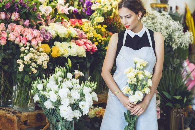 Female florist holding yellow roses in flower shop