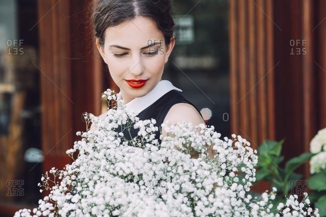 Female florist holding white flowers outside flower shop