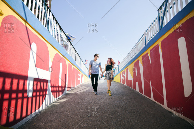 Young couple holding hands while walking on footpath against clear sky