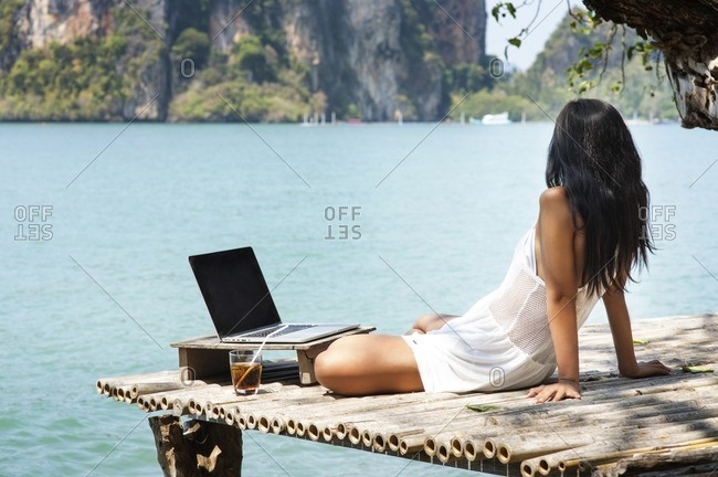 Woman with laptop computer sitting on wooden pier against sea
