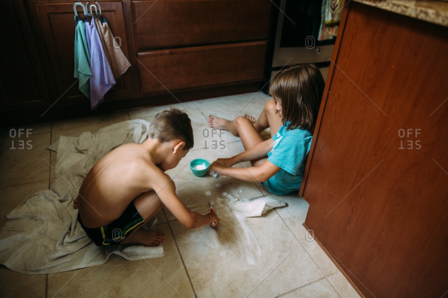 Two children scrubbing grout with toothbrushes