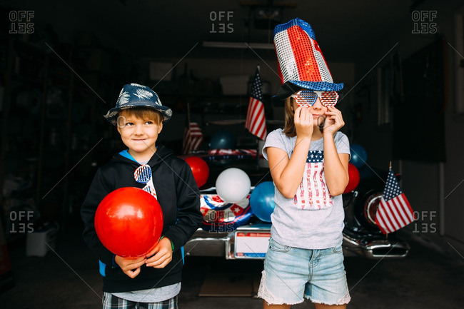 Boy and girl in garage with car decorated for Independence Day parade