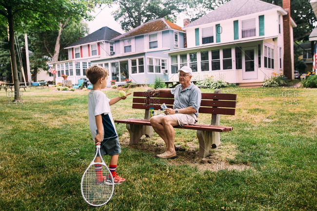 Boy with tennis racquet and ball talking to senior man on bench