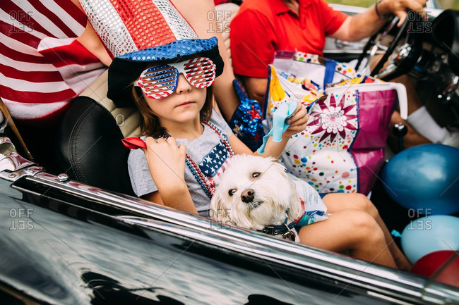 Girl in red, white and blue regalia riding in convertible with dog