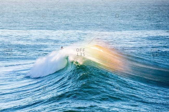 Surfer surfing on a rainbow colored wave
