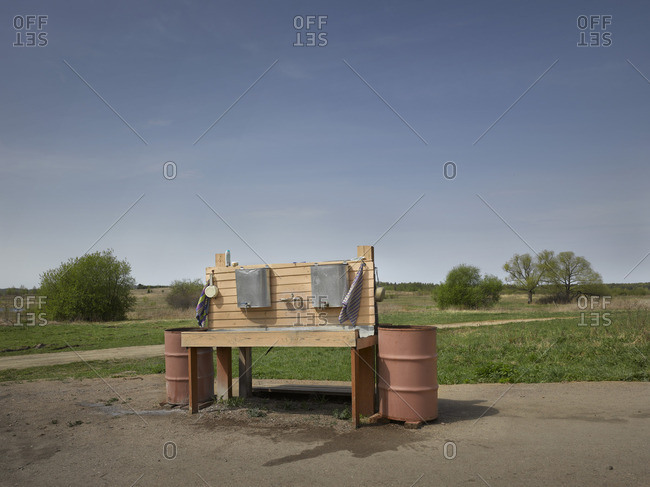 An outdoor wash basin near a tree lined field