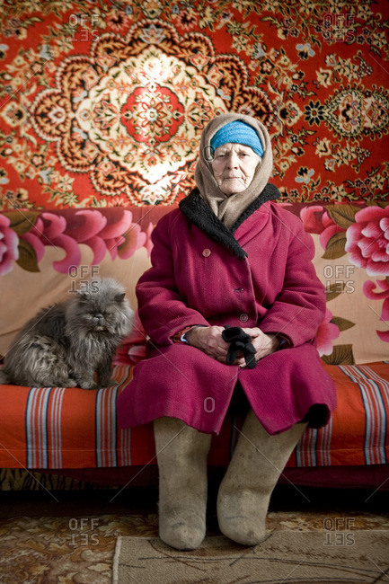 January 20, 2010: Portrait of a mature Russian woman sitting on a couch with her cat