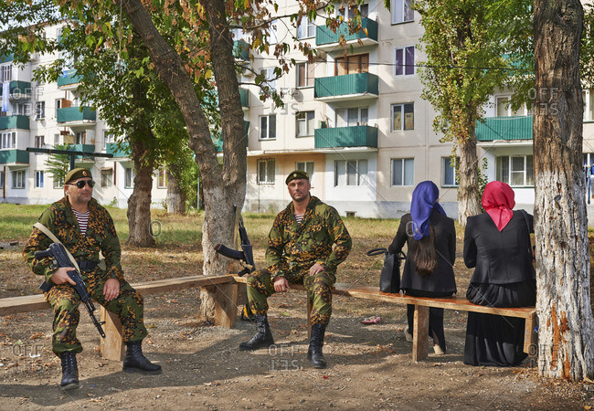 October 7, 2015: Two soldiers sitting on benches next to two women in Grozny, Chechen Republic, Russia
