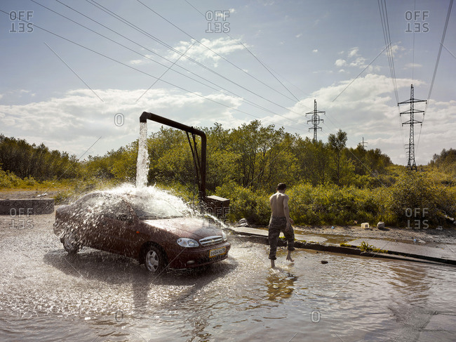 February 7, 2006: Man wading through water next to a car being washed under an outflow pipe