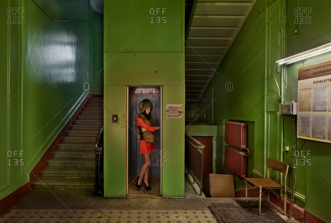 March 7, 2015: Woman in a dress, high heels and a fur hat using an elevator in a building in Kirov, Russia