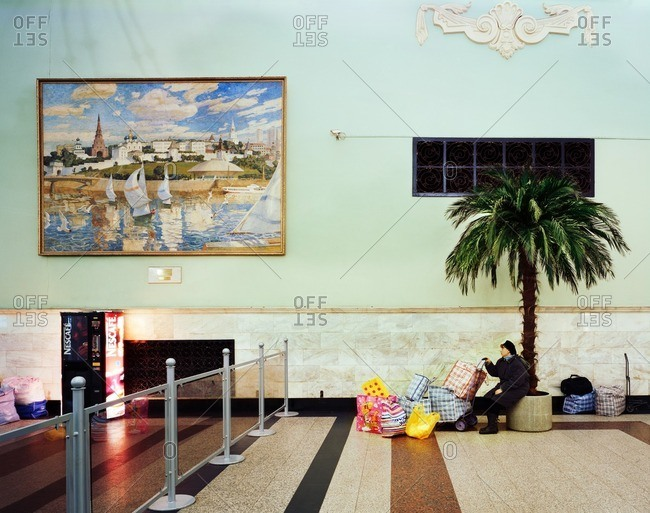 February 15, 2007: Woman with shopping bags sitting on a palm tree planter in a building lobby