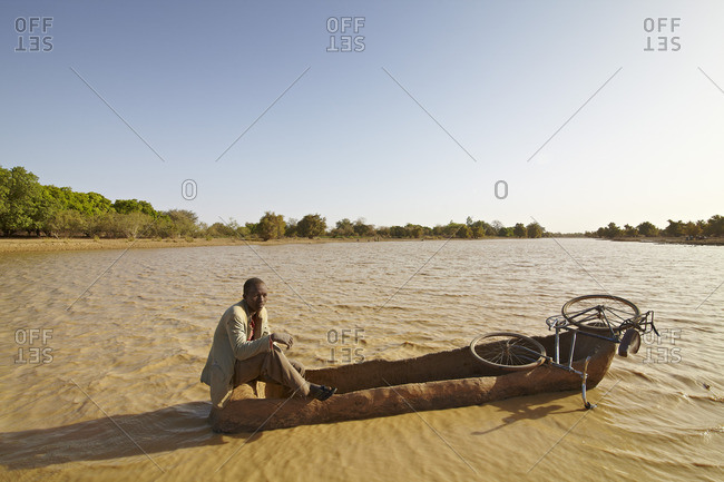 March 11, 2012: A man and his bicycle crossing a muddy river in a makeshift canoe