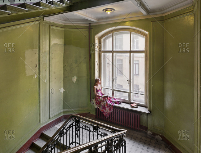 February 8, 2015: Woman sitting on a windowsill reading in an art deco residence in St. Petersburg, Russia