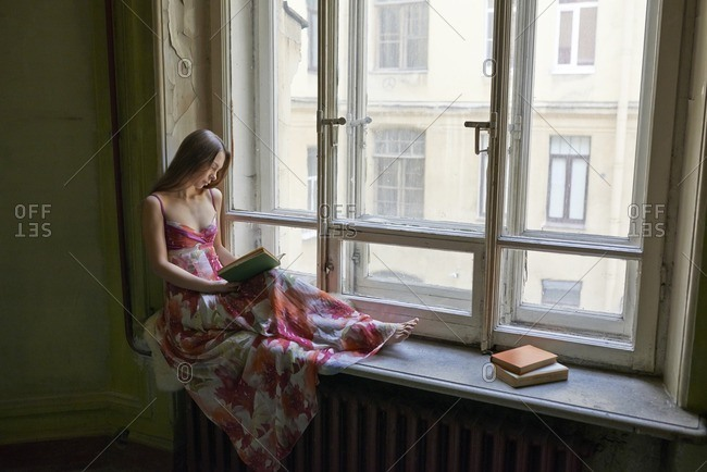 February 8, 2015: Woman sitting on a windowsill reading a book in an art deco residence in St. Petersburg, Russia