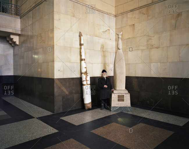 August 18, 2016: Man standing in a marble building lobby next to a statue