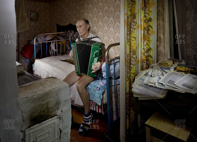February 7, 2006: Man playing accordion in his apartment room in the town of Budushee, Russia