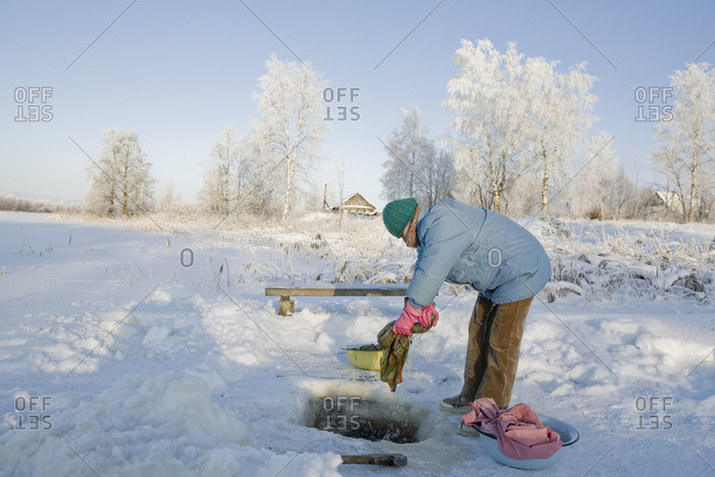 January 21, 2010: Woman washing her clothes in an icy lake near Budushee, Russia
