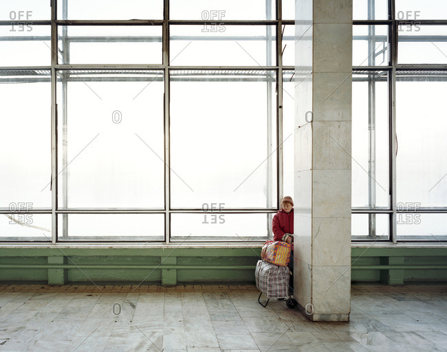 August 19, 2005: Woman holding a cart filled with bags standing near a pillar in an empty building