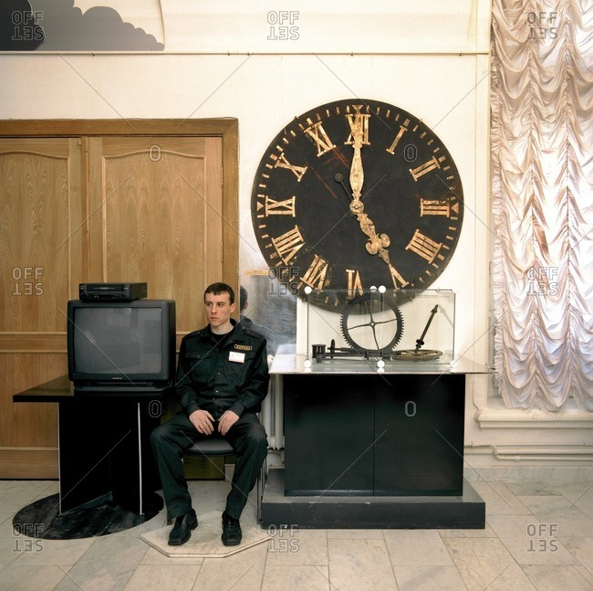 August 22, 2005: Man wearing a uniform sitting next to a large clock and a television