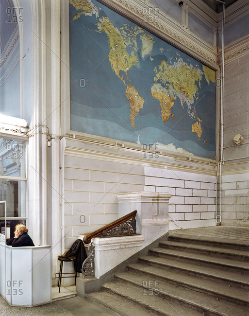 January 15, 2006: Woman sitting at a desk under a world map in a building in St. Petersburg, Russia