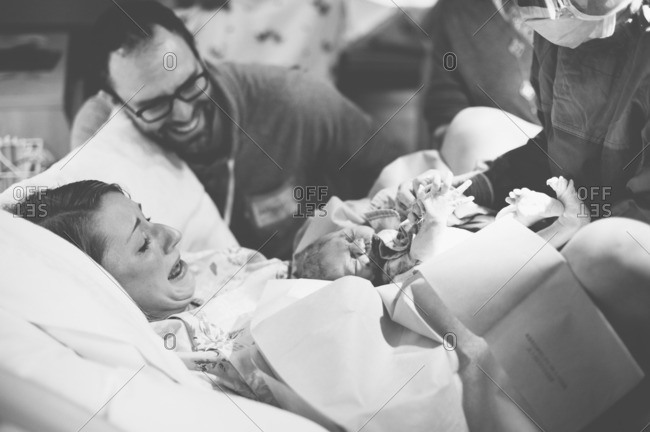 Emotional new parents meet their baby in hospital delivery room